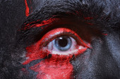 Male blue eyes bright with war paint — Stock Photo