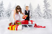 Children carry a heap of gifts on a sledge. — Stock fotografie