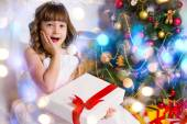Beautiful girl near the decorated Christmas tree, holds a white  — Stock Photo