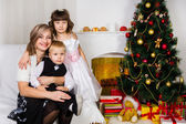 Happy mother and two her children in Christmas — Stok fotoğraf