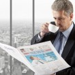 Businessman reading a newspaper — Stock Photo #64439377