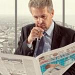 Businessman reading a newspaper — Stock Photo #71367871