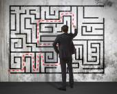 Businessman drawing labyrinth on wall — Stock Photo