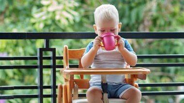 Toddler boy thirsty eagerly drinks a cup of yogurt — Stock Video