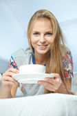 Woman with a cup of coffee on the bed — Stock Photo