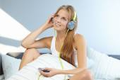 Woman lying on bed while listening music — Stock Photo