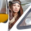 Beautiful woman pilot in front of airplane — Stock Photo #57267955