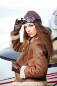 Beautiful woman pilot in front of airplane — Stock Photo