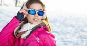 Woman wearing goggles in snowy winter — Stockfoto