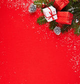 Red background with gifts and Christmas tree — Stock Photo