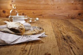 Vodka and dried fish on wooden table — Stock Photo