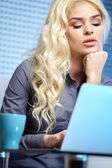 Portrait of happy blond woman using laptop  — Stock Photo
