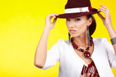 Fasionable woman in a hat over yellow — Stock Photo