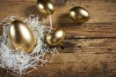 Golden eggs in nest on dark — Stock Photo