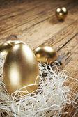 Golden eggs in nest on dark — Stock Photo