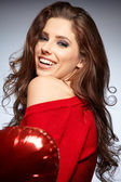 Beautiful woman holding red balloon — Stock Photo