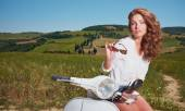 Woman sitting on a italian scooter — ストック写真