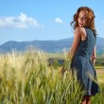 Woman in wheat field enjoying — Stock Photo #65437063