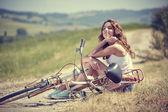 Niña sentada junto a la bicicleta — Foto de Stock