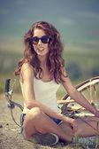 Menina sentada ao lado de bicicleta — Fotografia Stock