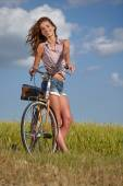 Woman with vintage bike in a country road — Foto Stock