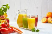 Healthy juices in grasses — Stock Photo