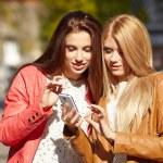 Women looking photos on smartfon — Stock Photo #68220273