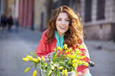 Girl sitting on bicycle with flowers — Stock Photo