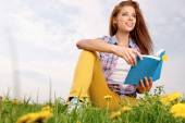 Woman on green field and reading book — Stock Photo
