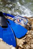 Mask and flippers on a rock beach — Stock Photo