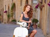 Beautiful woman sitting on scooter — Stock Photo