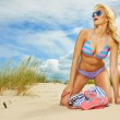 Blonde haired girl in bikini on  beach — Stock Photo #78396996