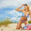 Blonde haired girl in bikini on  beach — Stock Photo #78397002
