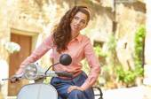 Beautiful woman sitting on a vintage scooter — Stock Photo