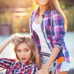 Two happy beautiful teen girls driving shopping cart outdoors — Stock Photo #51930041