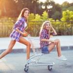 Two happy beautiful teen girls driving shopping cart outdoors — Stock Photo #51930061