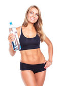 Young athletic girl with bottle of water on white — Stockfoto