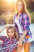 カートの屋外ショッピング運転 2 つの幸せな美しい 10 代の女の子 — ストック写真
