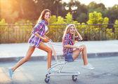 Two happy beautiful teen girls driving shopping cart outdoors — Stock Photo