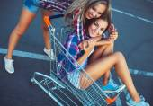 Two happy beautiful teen girls driving shopping cart outdoors — Stock Photo