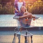 Two happy beautiful teen girls driving shopping cart outdoors — Stock Photo #52488595