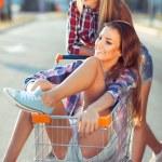 Two happy beautiful teen girls driving shopping cart outdoors — Stock Photo #52488597
