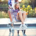 Two happy beautiful teen girls driving shopping cart outdoors — Stock Photo #52488601