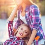 Two happy beautiful teen girls driving shopping cart outdoors — Stock Photo #52488607