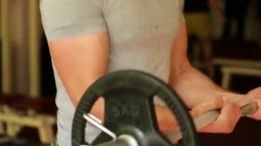 Athletic man trains arms at the gym — Wideo stockowe
