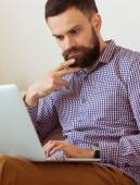 Young bearded man working on laptop — Stock Photo