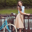 Young beautiful, elegantly dressed woman with bicycle — Stock Photo #60275531