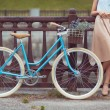 Young beautiful, elegantly dressed woman with bicycle — Stock Photo #60275559