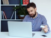 Young bearded man pays by credit card online shopping — Stock Photo