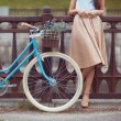 Young beautiful, elegantly dressed woman with bicycle — Stock Photo #61533641